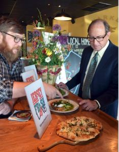 Ben Menk (left), General Manager of the Farm and Fisherman Tavern in Cherry Hill shows Secretary Fisher some of their dishes featuring Jersey Fresh ingredients.